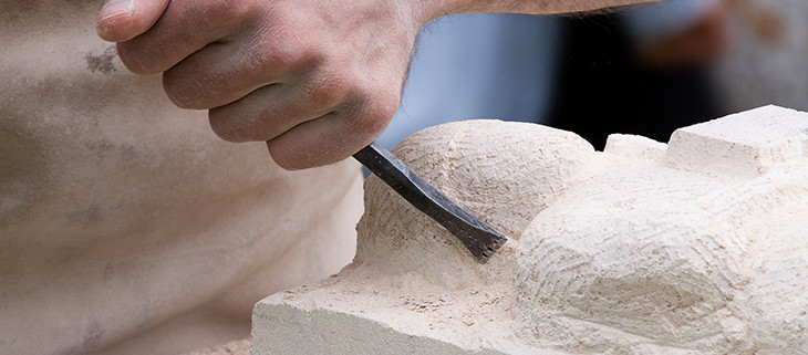 Mason carving out limestone